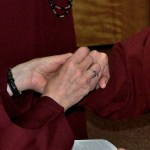 Mother Prioress slips the ring of solemn profession on the hand of a Handmaid.