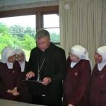 Bishop Stika shows the Sisters his iPad.