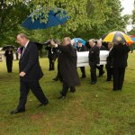 Pall bearers bring in the caskets.