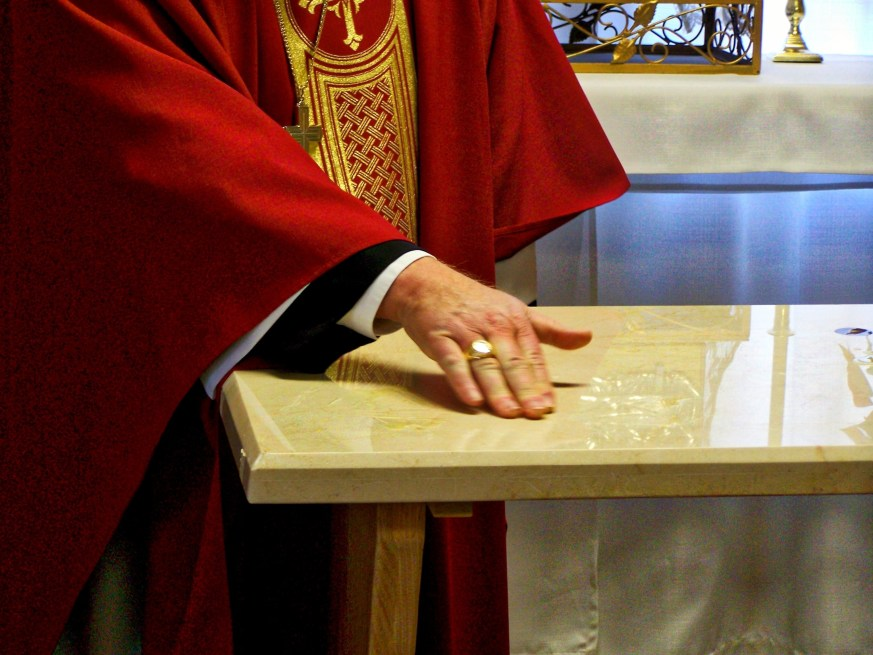 Marking the sign of the cross on the marble.