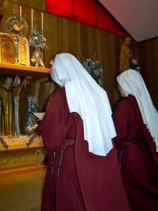 Two Handmaids kneel before the Lord upon the high altar.