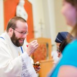 Father Ray Powell distributing Holy Communion