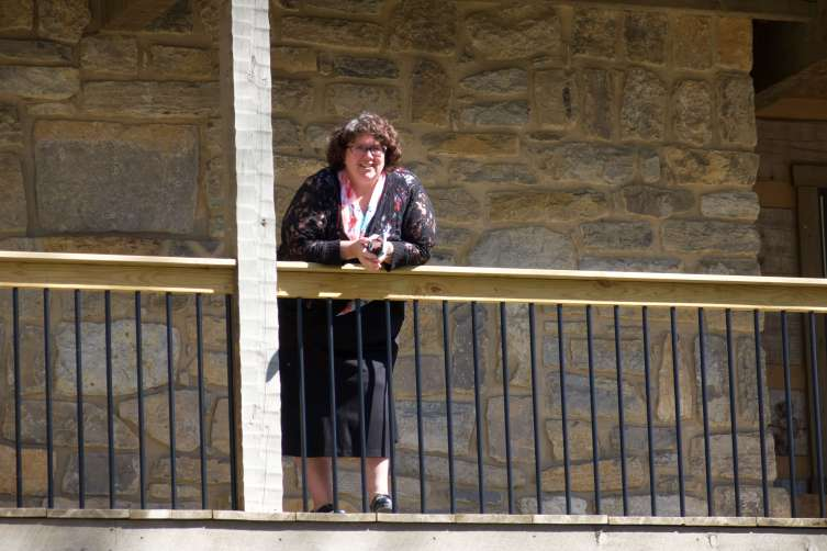 Peggy Humphreys, Bishop Stika's secretary, enjoys a birds-eye view from the deck of Cor Jesu Monastery during the long burial process.