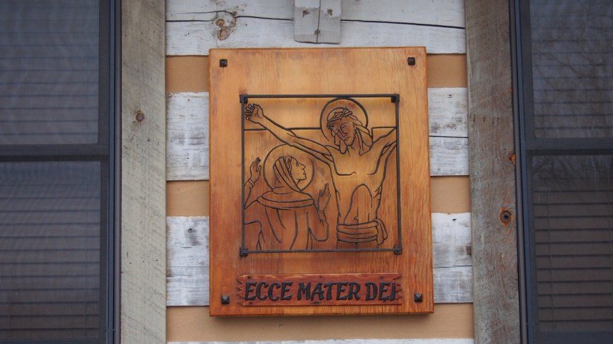 Mary, our Mother and our Model, stood beneath the Cross. This sign hung on the front of Cor Jesu Monastery in New Mexico for many years.