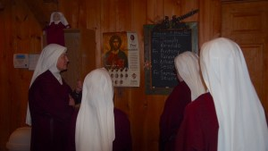 Mother shows the arriving Sisters the refectory board with priests names on it for this week and the Diocesan seminarian poster.