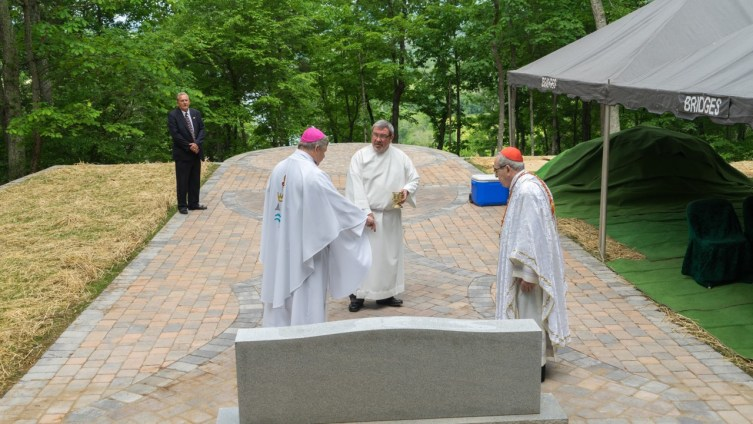 Bishop Stika and Cardinal Rigali examine the finished paving stones depicting a Chalice and Host. The cremains Bishop Stika drove across country are in the grave located under the stem of the Chalice.