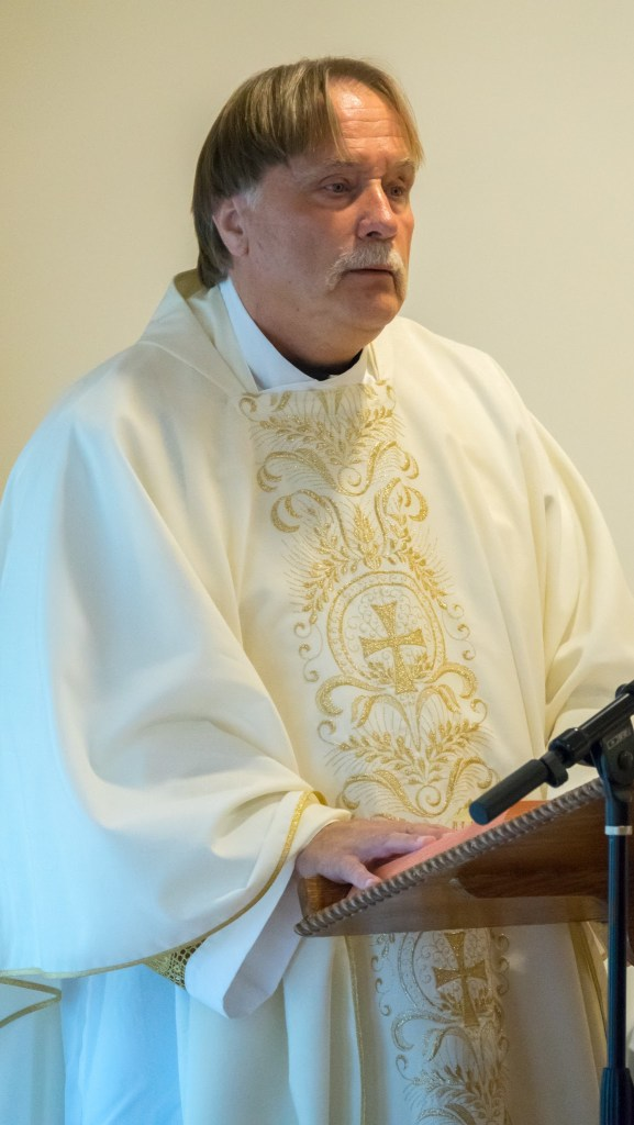 Father Ron Stone reads the Gospel