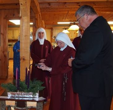 Sister lights the Advent Wreath just after Bishop Stika blessed it.