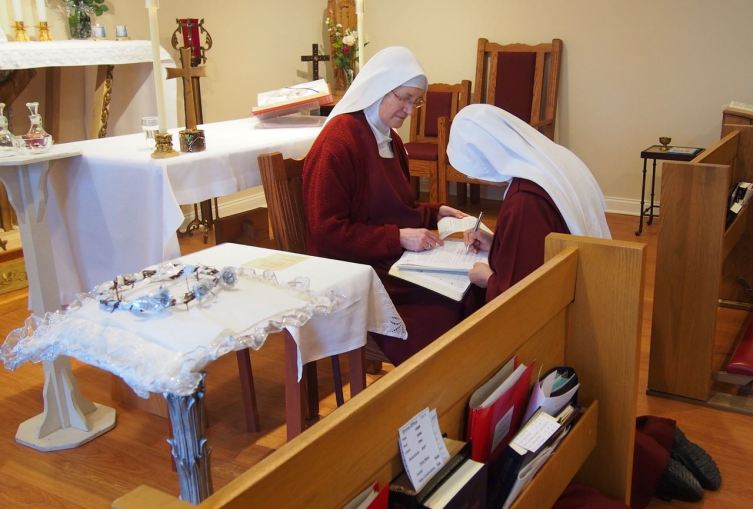 Sister kneels before the Mother Prioress to recite and sign her vow formula which lies on an open book of the Gospels.