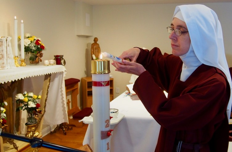 Lighting her baptismal candle from the paschal candle