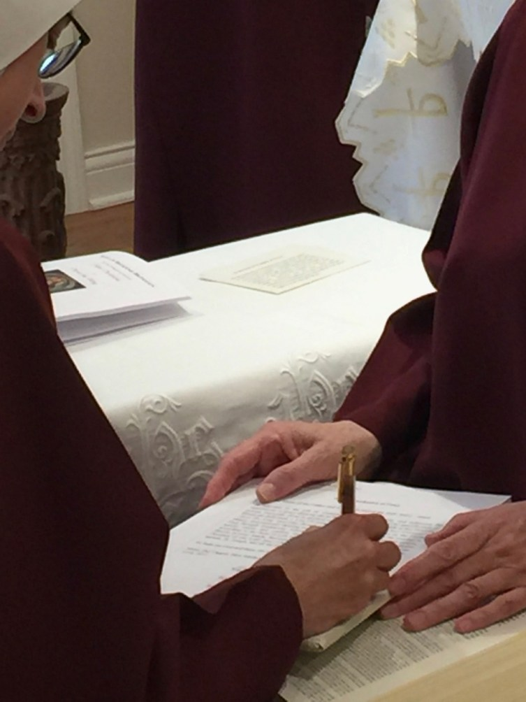 Sister signs the vow formula on top of the Holy Gospels