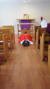 Father prostrates before the stripped altar and empty tabernacle