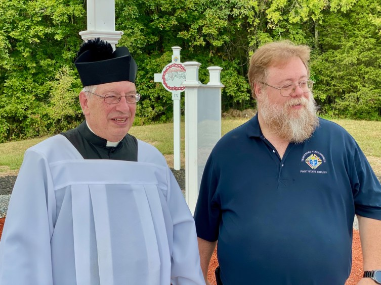 Father Patrick Resen and Past TN State Deputy Tracy Staller look on as names are placed in the garden.