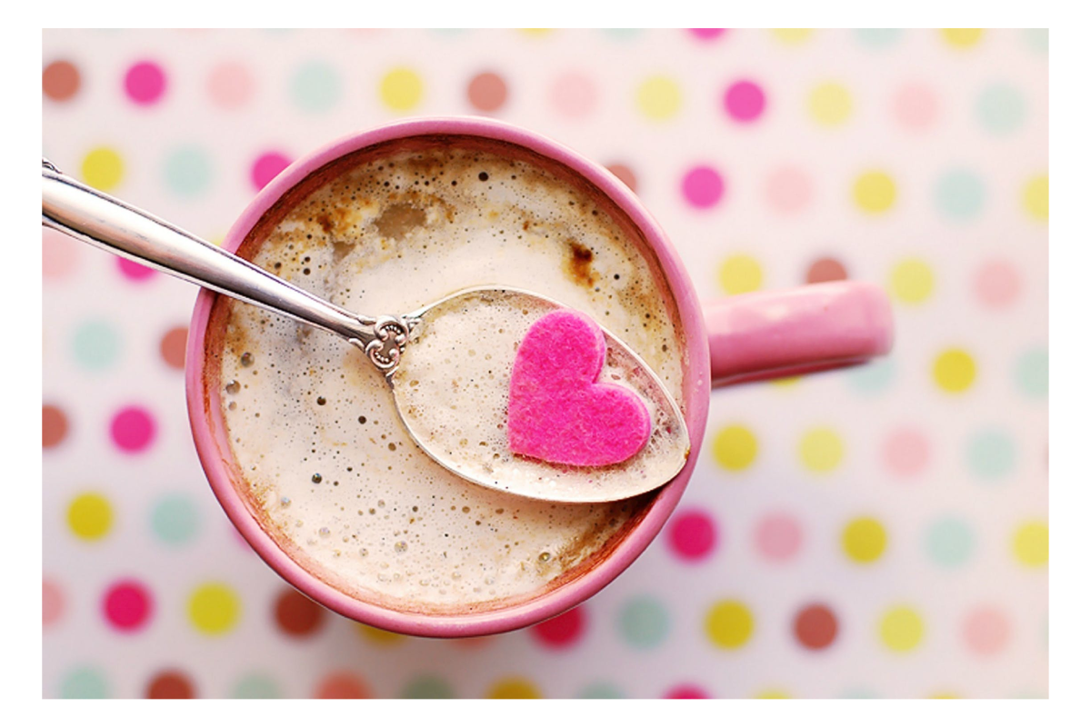 A cup of hot chocolate set out in front of a polkadot background.
