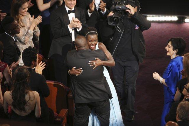 Steve McQueen e Lupita Nyongo'o si abbracciano dopo l'Oscar a 12 anni schiavo.
