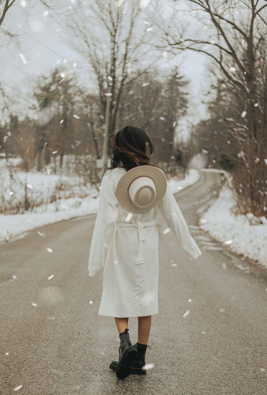 slim stylish woman on asphalt road near leafless trees
