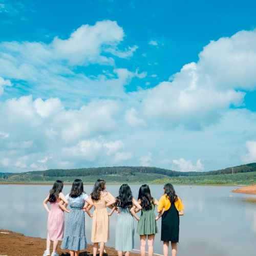 six women facing body of water taking picture