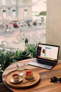 tray of fruits and coffee near powered on laptop on brown table