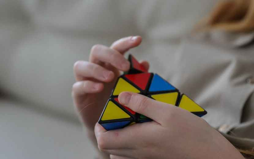 unrecognizable girl twisting combination puzzle at home
