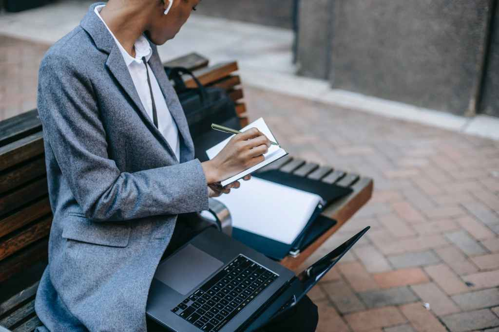 crop black lady sitting near city buildings and working remotely