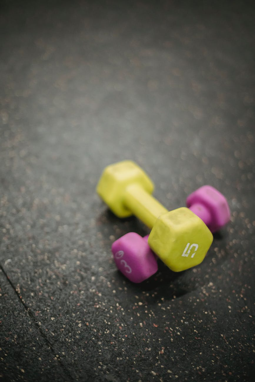multicolored fitness dumbbells on gray background