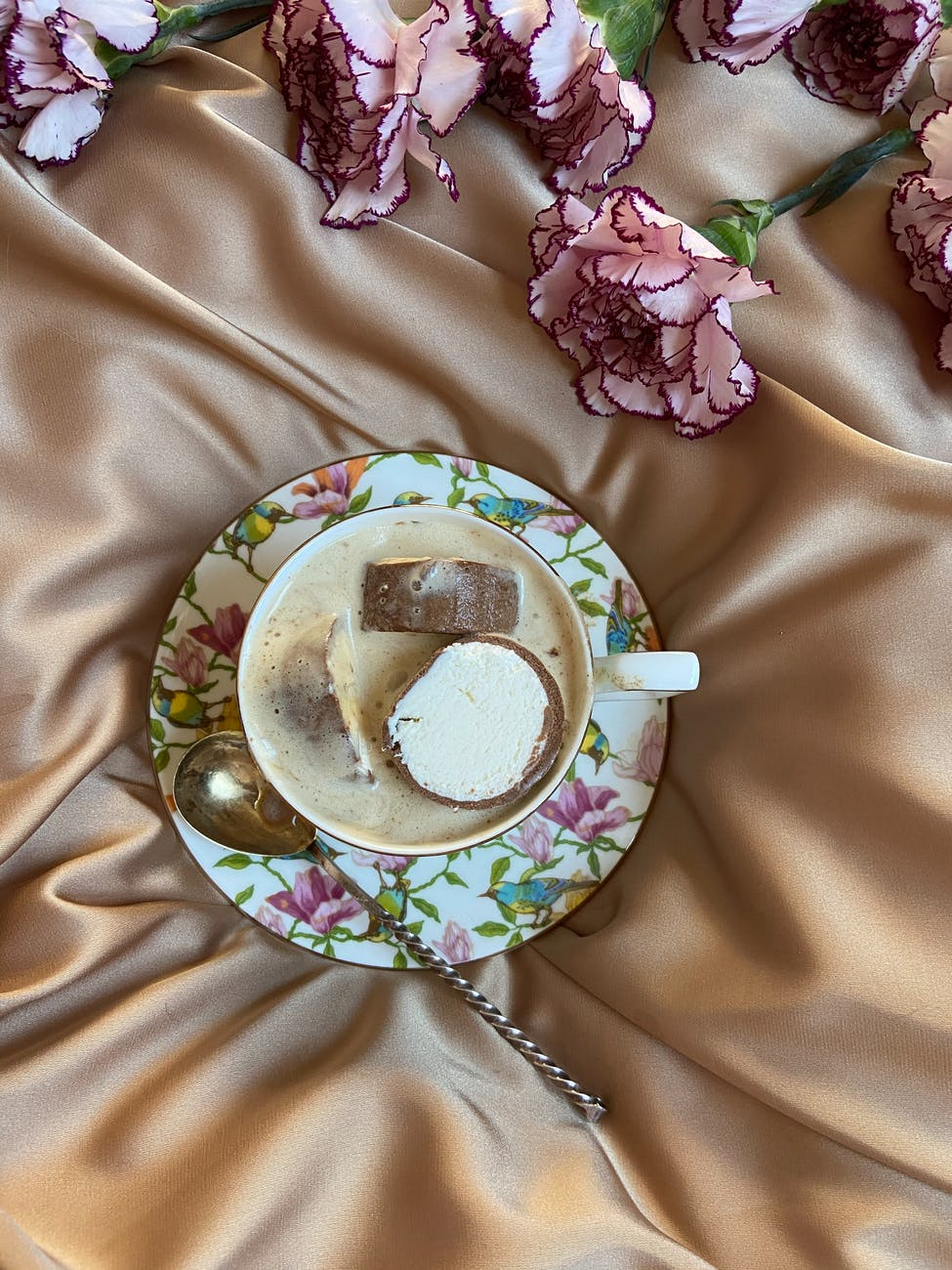 cup of coffee with ice cream on textile
