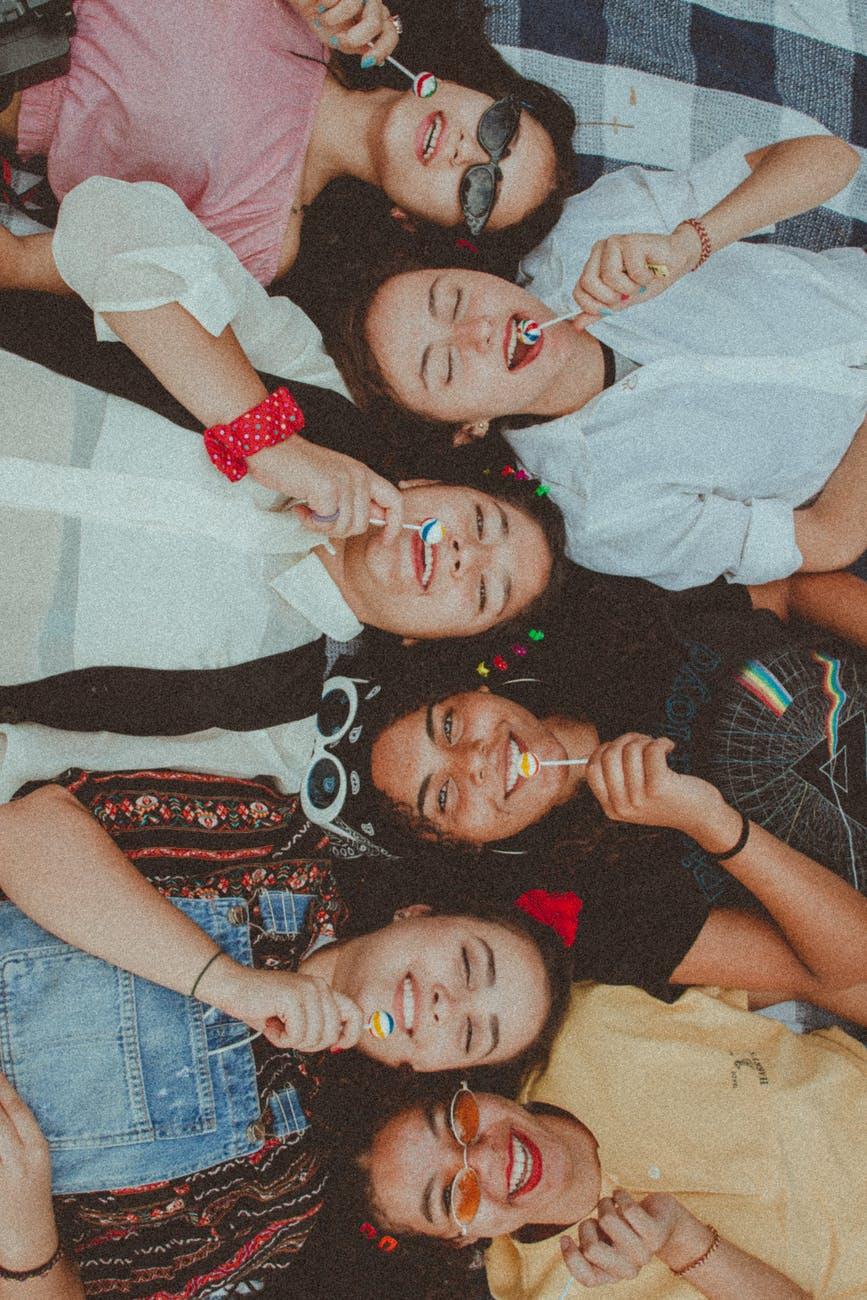 women lying down eating lollipop