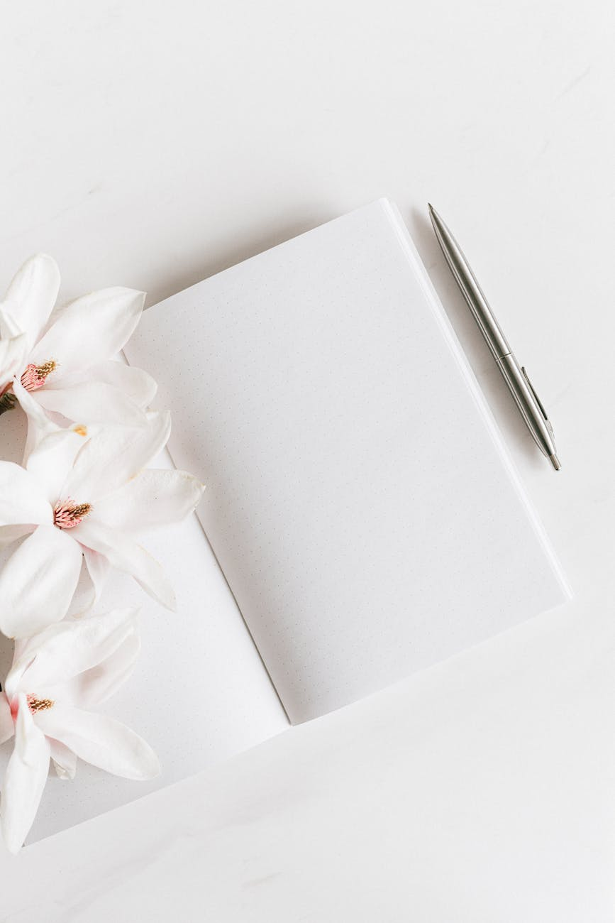 opened notebook with silver pen near magnolia