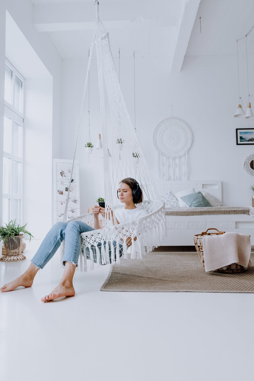 girl in white shirt and blue denim jeans sitting on white sofa chair