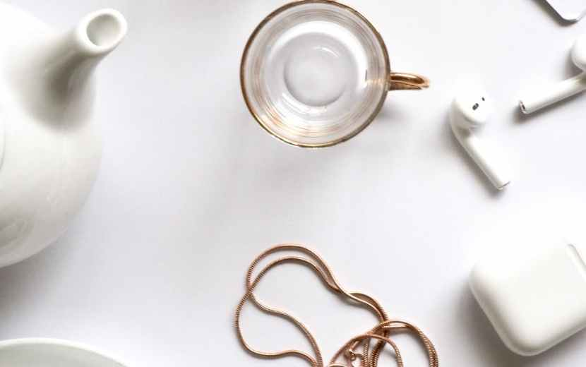 gold colored heart pendant necklace beside two glass mugs on table