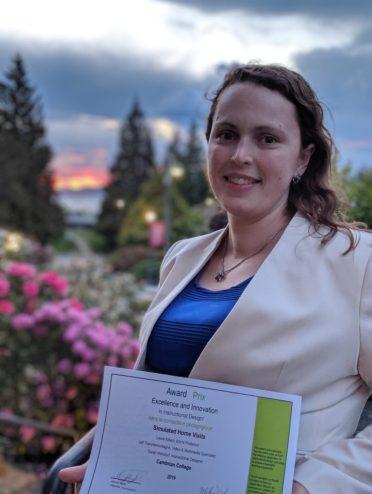 Laura Killam holding an award from CNIE.