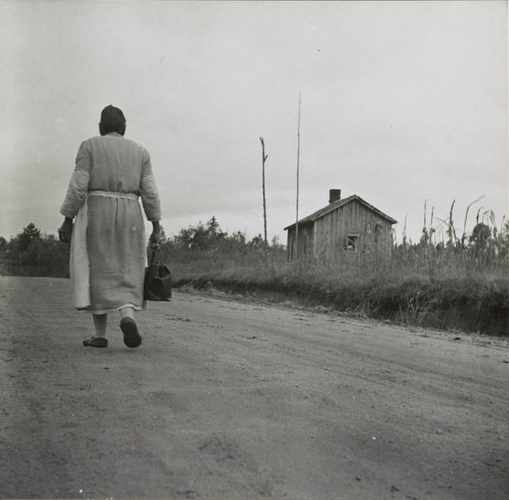 A Black woman in a dress and apron walks away from the camera down a dirt road. A small house is in the distance