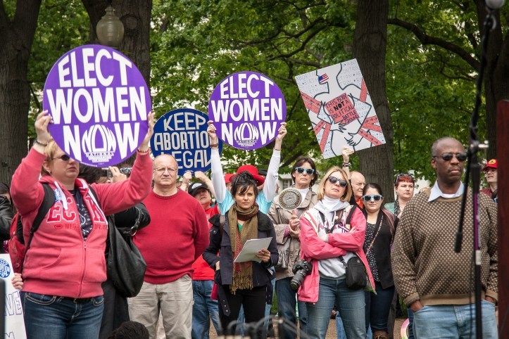 Group of protesters with signs to elect women