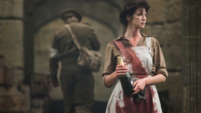 Outlander still frame with Clair holding a bottle in a bloddied apron