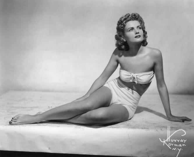 Rita J. Tennant poses in a white bikini