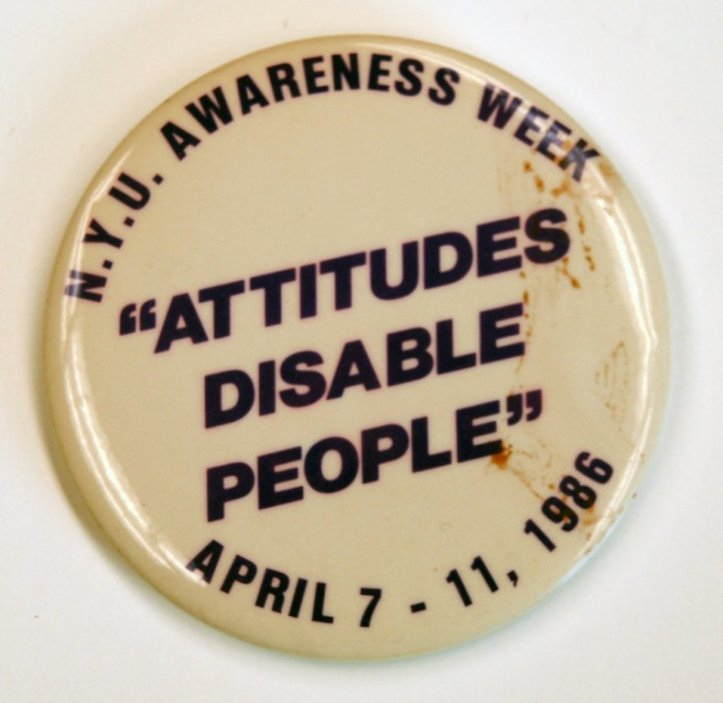 "NYU Awareness Week, ""Attitudes Disable People"" button, 1986. (EveryBody: An Artifact History of Disability in America/Smithsonian, National Museum of American History)"