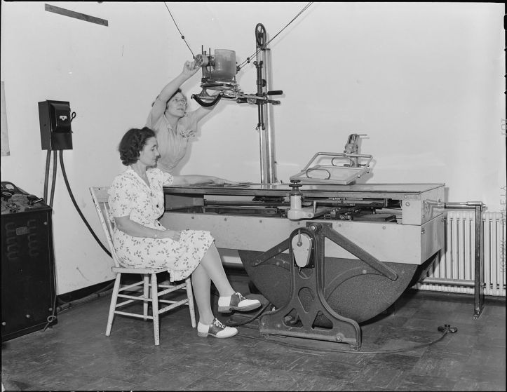 Nurse adjusting an x-ray machine to scan and photograph a woman's arm, in 1946 or 1947. (Lee Russell/National Archives and Records Administration id. 540951 | Public domain)