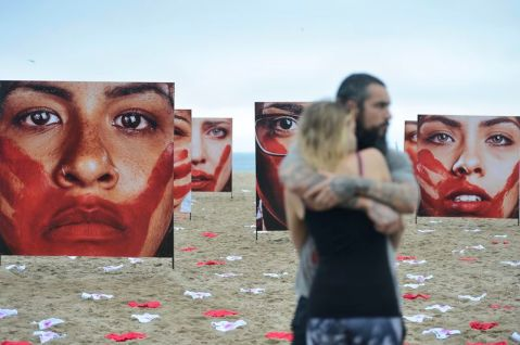A Rio de Paz protest at Copacabana beach, with 420 pairs of underwear -- the number of women raped every 3 days in Brazil according to organizers -- scattered among large photos of women with a handprint covering their mouths. (Tânia Rêgo/Agência Brasil)