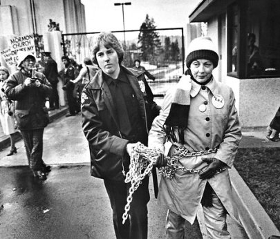 Sonia Johnson led away after chaining herself to the gate of a Mormon temple in Bellevue, WA, in 1980. (AP)