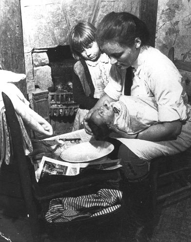 A photo of a Frontier Nursing Service nurse-midwife bathing a newborn. (University of Kentucky Photographic Archives)