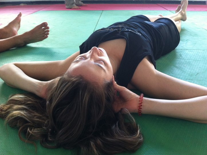 Woman laying on a green mat with hands behind head and legs crossed.