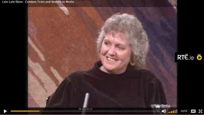 Older white woman with curly gray hair smiles in a mock turtle neck