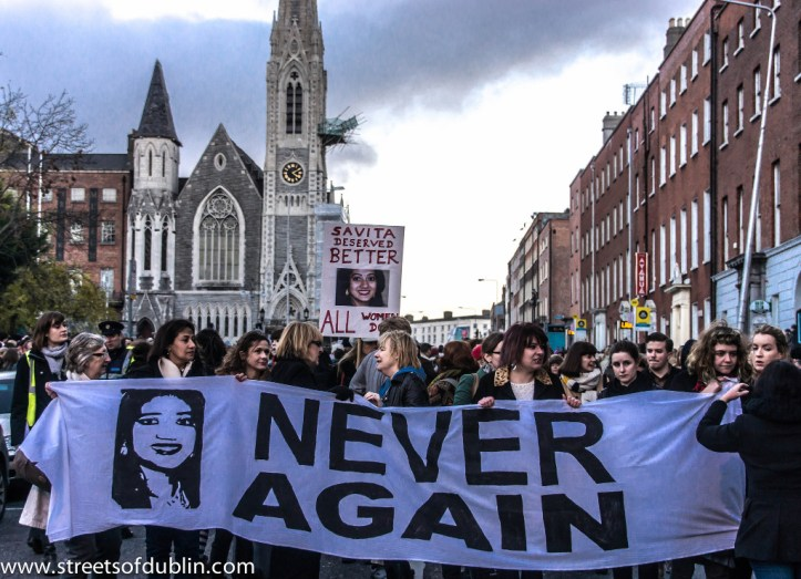 A crowd on a Dublin street holds up a purple banner with a picture of Savita Halappanavar spray painted on it and the words NEVER AGAIN next to her picture