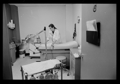 A white woman in a lab coat adjusts a sheet on a hospital bed inside a room, with an empty instruments table nearby and a chart folder on the wall