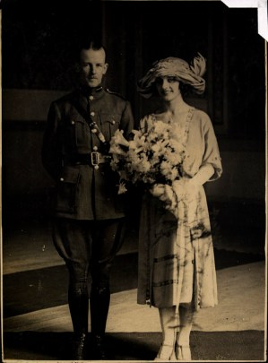 A white couple stands together, a man in a soldier's or police uniform, woman in a light colored dress with a big hat and a bouquet of flowers.