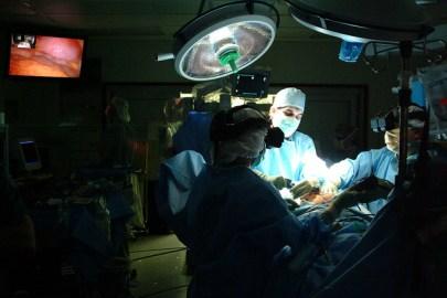 Three surgeons around an operating table, an overhead light illuminates iodine prepped skin.