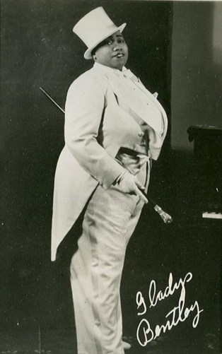 Full length portrait of an African American person in a white tuxedo and top hat