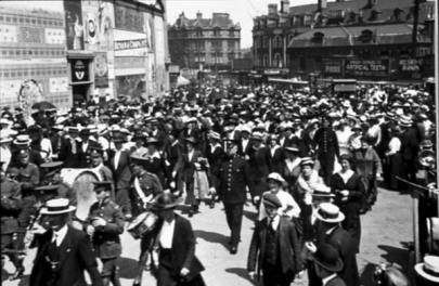 A crowd of men and women mill about, dressed for traveling in coats, hats, and most carrying bags.