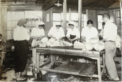 Black and white photo of students cutting vegetables around a table