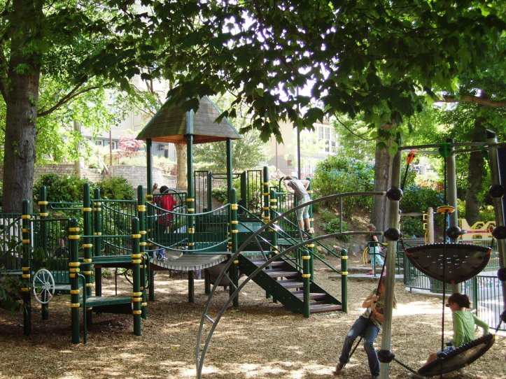 Jungle gym shaded by trees. Children play on swings and climb ladders.
